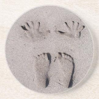 La mano y los pies imprime en arena de la playa de posavasos manualidades