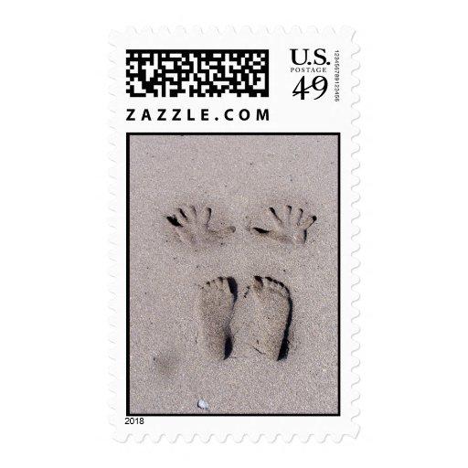 La mano y los pies imprime en arena de la playa de sellos