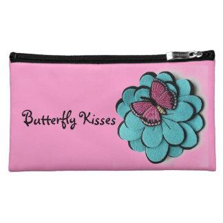 La mariposa besa el bolso medio del cosmético del