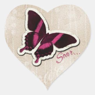 La mariposa rosada se eleva en fondo beige pegatina en forma de corazón