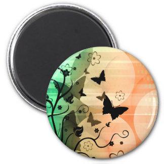 La mariposa siluetea el imán anaranjado y verde