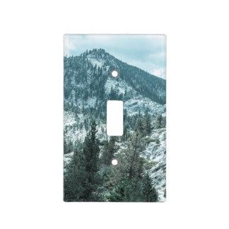 La montaña rocosa con los árboles acerca al lago tapa para interruptor