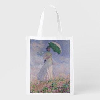 La mujer con un parasol dio vuelta a la derecha, 1 bolsa para la compra