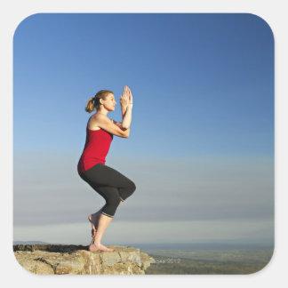 la mujer joven practica yoga en un pen¢asco en calcomanía cuadrada personalizada