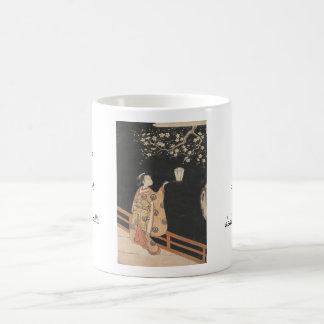 La mujer joven que admira el ciruelo florece en el taza clásica