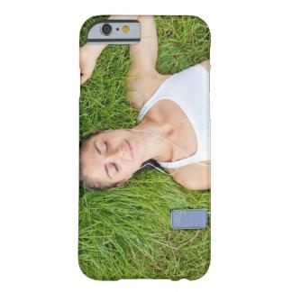 La mujer se relaja con música en hierba suave
