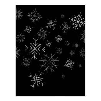 La nieve blanca forma escamas en el cielo negro tarjeta postal
