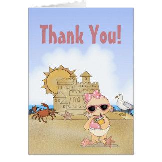 La niña fresca de la playa con el castillo de tarjeta pequeña