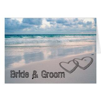 La novia y el novio nombra escrito en la arena felicitacion