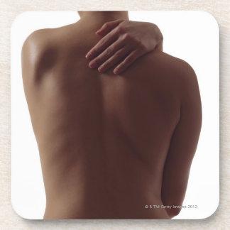 La parte posterior desnuda de una mujer con un alc posavasos
