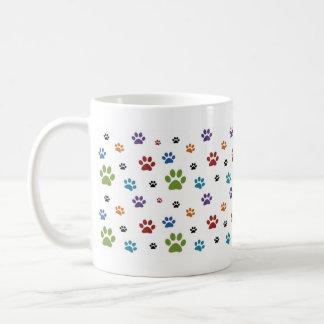 La pata colorida del perro imprime la taza