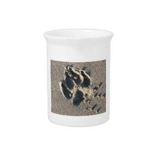 La pata-impresión del perro en la arena jarras de beber