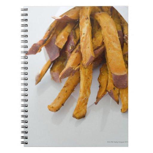 La patata dulce fríe en la bolsa de papel, cierre  libreta espiral