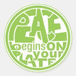 La paz del lema del vegano comienza por su placa etiquetas redondas