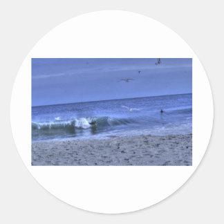 La persona que practica surf del cuerpo coge una pegatina redonda