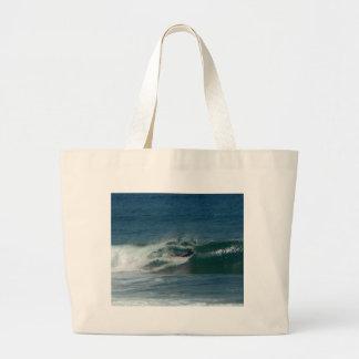 La persona que practica surf encendido ve bolsa tela grande