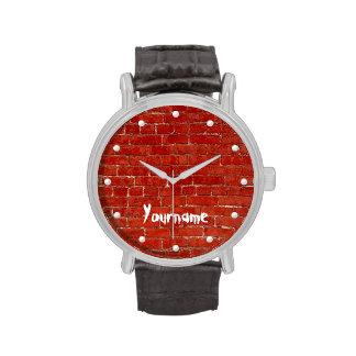 La pintada roja de la pared de ladrillo añade su relojes de mano