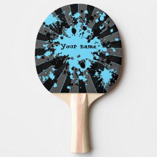 La pintura azul salpica negro y el gris pala de tenis de mesa