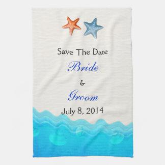 La playa con las estrellas de mar ahorra la fecha toalla de cocina