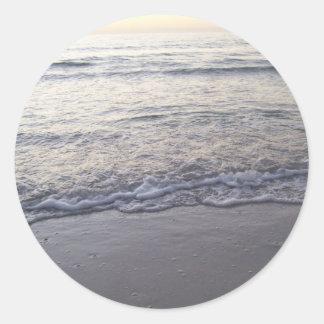 La playa en la puesta del sol etiquetas redondas