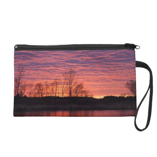 La puesta del sol brillante refleja en el río del