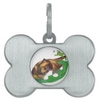 La rana salta sobre la cola del gatito del calicó placas de nombre de mascota
