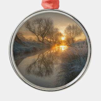 La salida del sol consume la niebla de la adorno redondo plateado