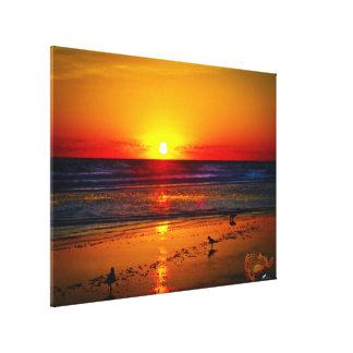 La salida del sol y el océano es reflexión en la lienzo envuelto para galerías