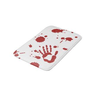 La sangre sangrienta de la mano salpicó la estera