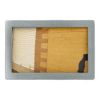 La sombra de un hombre en la pared iluminada de un hebillas de cinturon rectangulares
