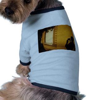 La sombra de un hombre en la pared iluminada de un camiseta con mangas para perro