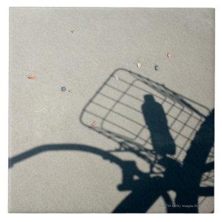 La sombra de una bicicleta con una botella de agua azulejo cuadrado grande