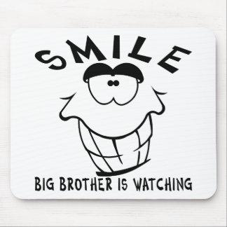 La sonrisa hermano mayor está mirando tapetes de ratón