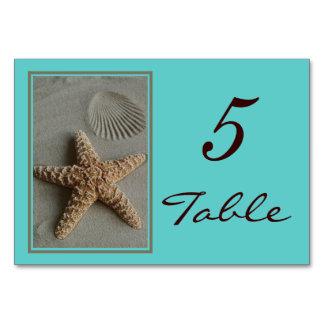 La tabla del boda del tema de la playa numera