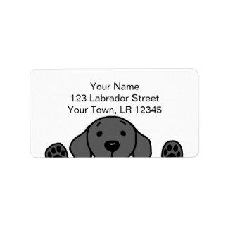 Labrador negro que le mira etiquetas de dirección