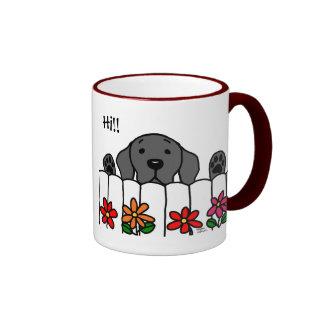 Labrador negro que le mira taza de café