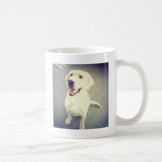 Labrador retriever amarillo cariñoso de la taza de café