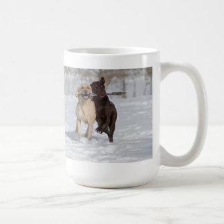 Labradores retrieveres que juegan en la nieve tazas de café