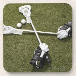 Lacrosse sticks, gloves and balls on artificial beverage coaster