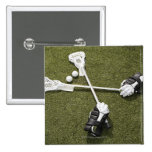 Lacrosse sticks, gloves and balls on artificial button