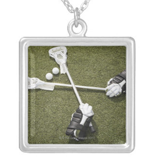 Lacrosse sticks, gloves and balls on artificial silver plated necklace