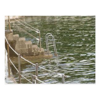 Ladder descending into the sea water postcard