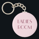 "Ladies restroom keyring<br><div class=""desc"">Keychain with a dark purple text on a pink background: Ladies room.</div>"