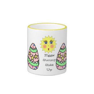 Lado soleado de los huevos encima de la taza de Pa
