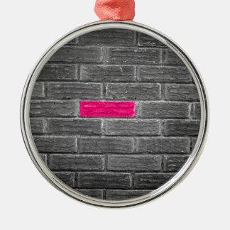 Ladrillo rosado en una pared negra y blanca adorno redondo plateado