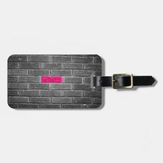 Ladrillo rosado en una pared negra y blanca etiquetas maletas