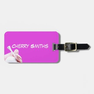 Lady golfer hand  is holding white tee on pink luggage tag
