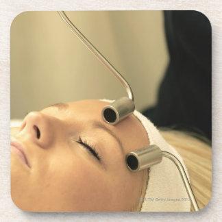 Lady having face massage beverage coaster
