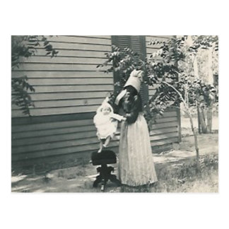 lady with bonnet putting child on seat postcard
