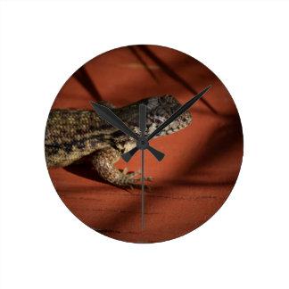 lagarto que mira abajo en el animal de madera del reloj redondo mediano